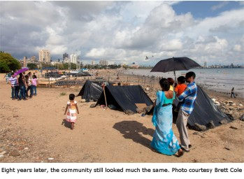 A family walks past squatter's tents on the beach