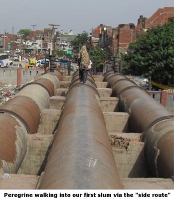Crossing a culvert to enter the slum